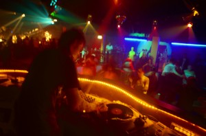 toned shot of a disc jockey playing music and people dancing in a discotheque