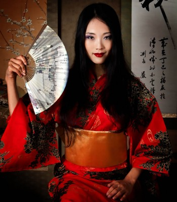 Beautiful Japanese geisha with a paper fan