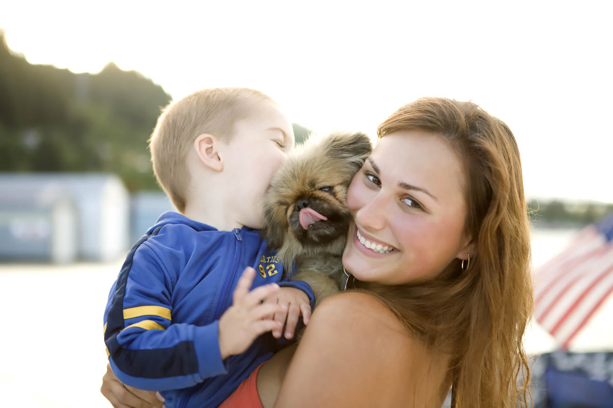 Woman embracing young son and dog outdoors