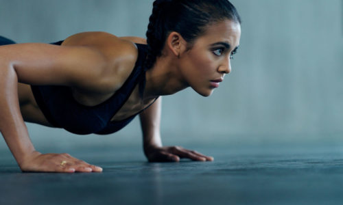 Shot of an attractive young woman doing push ups at the gym
